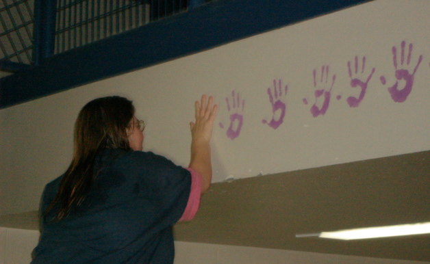 Women inmates paint their hands pledges in the common area after taking the Hands & Words Pledge together!