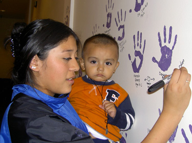 Mother takes Pledge with her son and signs her name on the wall along with hundreds of citizens in a permanent display at Salem Center Mall in downtown Salem, OR